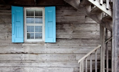 Wooden house with blue wooden window sun shades