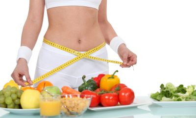 woman's torso in white mid-drift top and fruit on the table