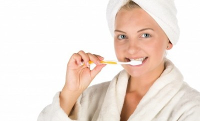 Woman in white bath rope and white towel on her wet hair brushing her teeth