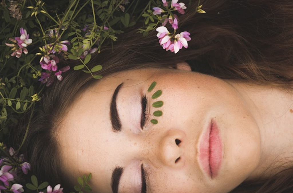 close . up of woman's face surrounded by flowers