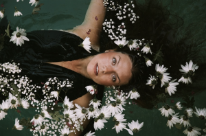 woman in clothes under water surrounded with flowers