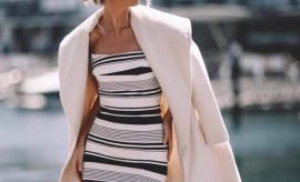 woman with stripped dress and a coat over her shoulders