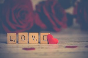 Four wooden cubes with LOVE word in them with a red heart at the end of the word