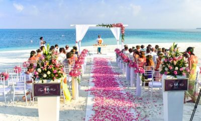 Beach wedding with pink rose petals on a white trail to the alter