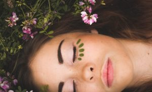 close up of a girl's face with closed eyes and flowers in her hair and