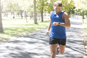 Man wearing blue tank top and black shorts jogging and checking his smartwatch