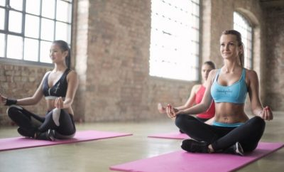 two women doing yoga in pink matts
