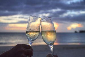 Two glasses of champagne raised in a sky horizon