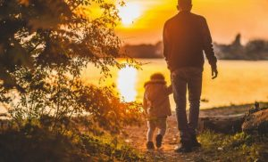 Man holding hands with a child walking in the sunset