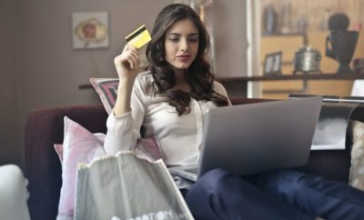 young woman using laptop at home holding a credit card