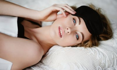 woman in bed with eye mask on her forehead