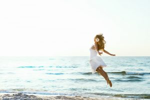 woman in white at beach flying