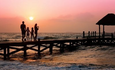 Family walking at dusk together by seaside
