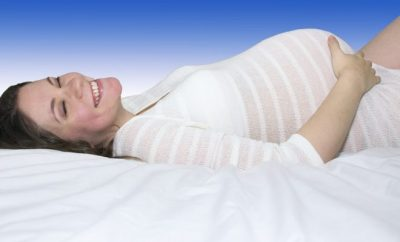 Pregnant woman on her back smiling at the camera