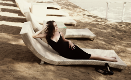 woman lounging at the beach with black high heels off