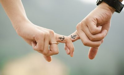 couple holding hands with a miniature anchor tattoo