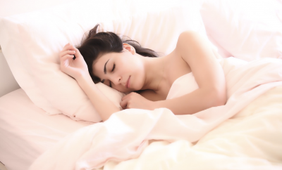 Woman asleep in bed with pale pink sheets