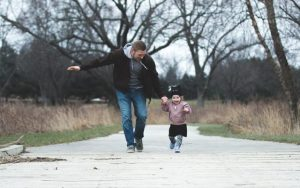 Father holding hands with a toddler while in the park
