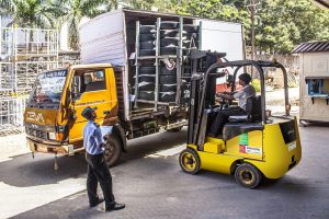 Forklifting operator filling a truck with goods