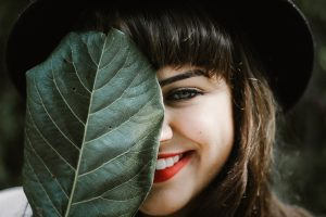 Smiling woman with a large green leaf covering her face