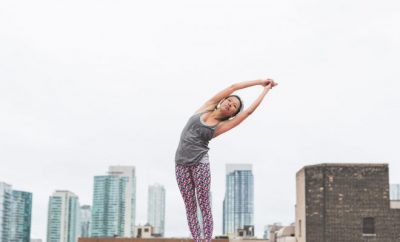 Woman stretching with a backdrop of a city behind her