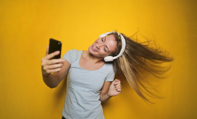 Woman taking a selfie with white headphones