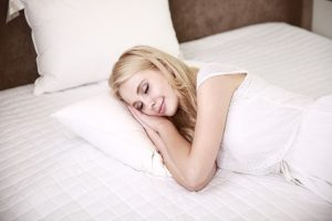 woman happily asleep in bed