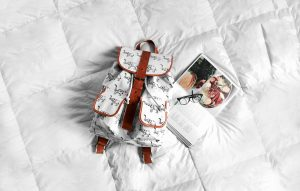 Elephant print, white backpack laying on a bed