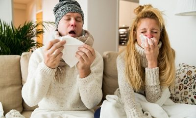 a couple blowing their noses wearing woollen jumpers