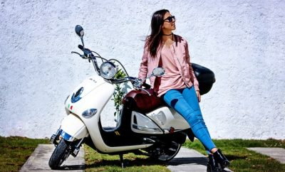 woman in blue jeans and pink leaning on a white scooter