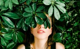 Woman hiding behind green leafy plant