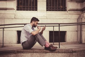 young man in business pants sitting on pavement on phone