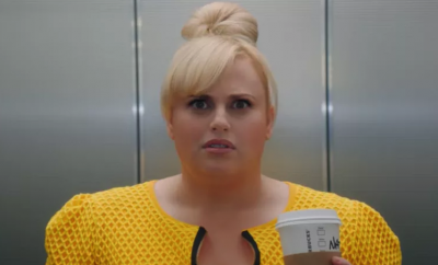 Rebel Wilson in yellow top looking surprised