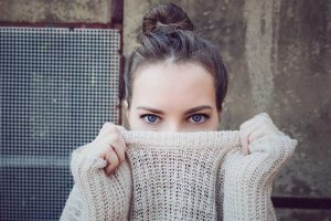 woman pulling sweater over her face