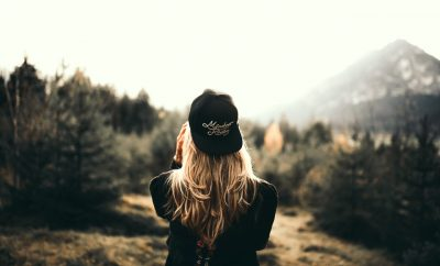 back shot of a blond woman wearing a cap looking onto hills