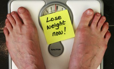 "feet on weighing balance with a yellow sticker note ""lose weight now"""
