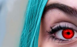 woman with blue hair wearing red contact lenses