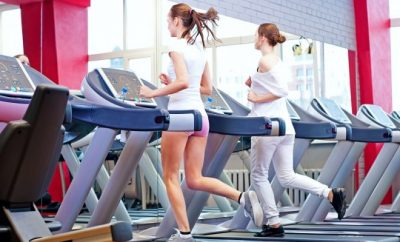 two women running on treadmills in a gym