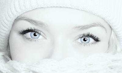 blue eyed woman with a scarf over her mouth and nose
