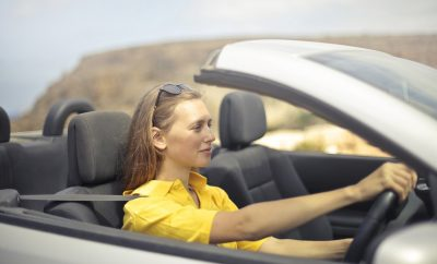woman in yellow top driving a car