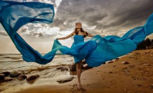 Lady walking on the beach with sky blue dress blowing in the wind