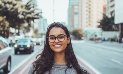 Young woman with glasses smiling at camera