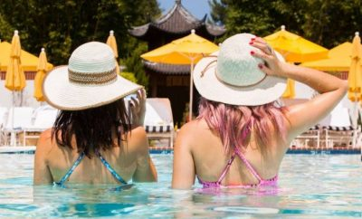 Two women submerged to their waist in pool wearing sun hats