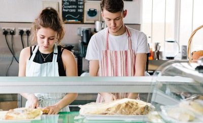 Young couple behind the counter preparing sandwiches