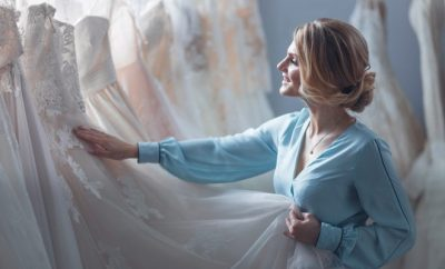 blond woman happily looking at a dress