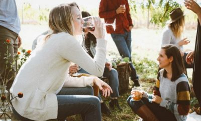 A group of people enjoying a glass of wine in a vineyard