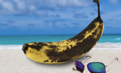 a banana with skin patches in the sand with a pair of sunglasses