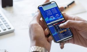 Businessman looking at stock exchange on his phone