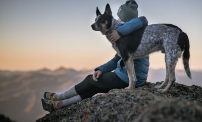 woman with her dog at the top of a mountain