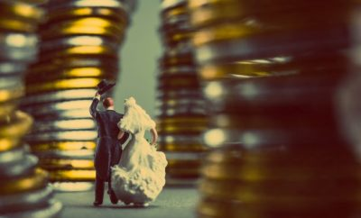 Bride and groom standing in front of pile of coins